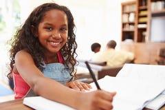 Портрет девушки делая домашнюю работу на таблице Стоковое фото RF
