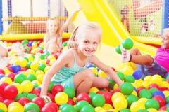 Портрет девушки играя в бассейне с пластичным пестротканым шариком Стоковое Изображение