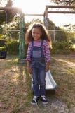 Портрет девушки играя Outdoors дома на скольжении сада Стоковое фото RF