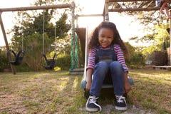 Портрет девушки играя Outdoors дома на скольжении сада Стоковое Изображение