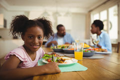 Портрет девушки имея еду на обеденном столе Стоковые Фотографии RF