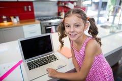 Портрет девушки используя компьтер-книжку в кухне Стоковые Фотографии RF