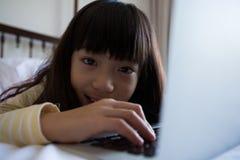 Портрет девушки используя компьтер-книжку на кровати дома Стоковая Фотография RF
