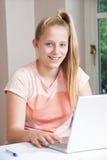 Портрет девушки используя компьтер-книжку дома Стоковые Фотографии RF