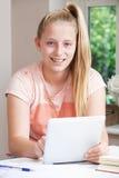 Портрет девушки используя таблетку цифров дома Стоковые Изображения
