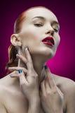 Портрет девушки красоты на фиолетовой предпосылке Стоковое Изображение