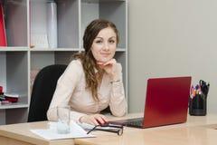 Портрет девушки на компьтер-книжке в офисе Стоковые Фото