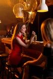 Портрет девушки дня рождения сидя с стеклом коктеиля на счетчике бара Стоковое Изображение