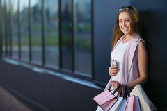 Портрет девушки покупок моды Усмехаясь девушка с хозяйственными сумками с телефоном в руке Концепция покупок женщины Стоковое Фото