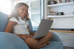 Портрет девушки при компьтер-книжка сидя на кресле Стоковые Изображения