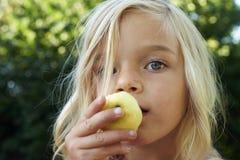 Портрет девушки ребенка белокурой есть яблоко outdoors Стоковая Фотография