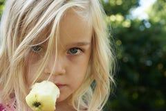 Портрет девушки ребенка белокурой есть яблоко outdoors Стоковые Фотографии RF