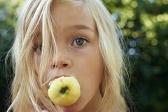 Портрет девушки ребенка белокурой есть яблоко outdoors Стоковое Изображение RF