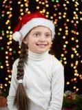 Портрет девушки ребенка в украшении рождества, одетом в шляпе Санты, boke освещает на темной предпосылке, концепции зимнего отдых Стоковое фото RF