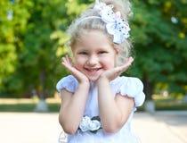 Портрет девушки ребенка, представляя в белой мантии, крупный план стороны, счастливая концепция детства, сезон лета в парке город Стоковые Фотографии RF