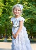 Портрет девушки ребенка, представляя в белой мантии, счастливая концепция детства, сезон лета в парке города Стоковая Фотография RF