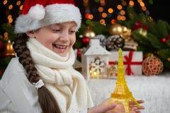 Портрет девушки ребенка с украшением figurine и рождества Эйфелевой башни, темная предпосылка с светами, выражение стороны и счас Стоковое Фото