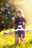 Портрет девушки сидя на деревянной скамье дует пузыри в th Стоковая Фотография