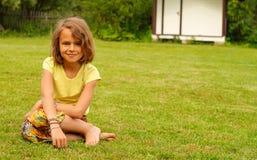 Портрет девушки 10 сидя на зеленой траве Стоковые Фотографии RF