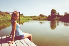 Портрет девушки сидя на мосте около воды Стоковые Изображения RF