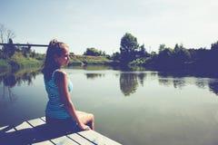 Портрет девушки сидя на мосте около воды Стоковые Фотографии RF