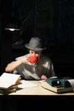 Портрет девушки сидя на таблице с машинкой и книгами, выпивая чаем на ноче Стоковая Фотография