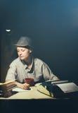 Портрет девушки сидя на таблице с машинкой и книгами, делая примечания на ноче Стоковое Изображение
