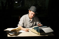 Портрет девушки сидя на таблице с машинкой и книгами, делая примечания на ноче Стоковое фото RF