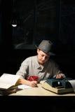 Портрет девушки сидя на таблице с машинкой и книгами, делая примечания на ноче Стоковые Изображения RF