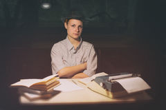 Портрет девушки сидя на таблице с машинкой и книгами, думает о идее на ноче Стоковое Изображение