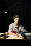 Портрет девушки сидя на таблице с машинкой и книгами, думает о идее на ноче Стоковые Фото