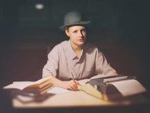 Портрет девушки сидя на таблице с машинкой и книгами, думает о идее на ноче Стоковое Изображение RF
