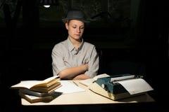 Портрет девушки сидя на таблице с машинкой и книгами, думает о идее на ноче Стоковые Изображения