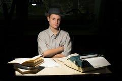 Портрет девушки сидя на таблице с машинкой и книгами, думает о идее на ноче Стоковая Фотография RF