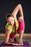 Портрет девушки спорта делая йогу протягивая тренировку на фиолетовой циновке йоги в спортзале Стоковое фото RF