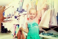 Портрет девушки стоя в магазине одежд детей с ходя по магазинам b Стоковое фото RF