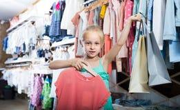 Портрет девушки стоя в магазине одежд детей с ходя по магазинам b Стоковые Изображения
