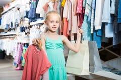 Портрет девушки стоя в магазине одежд детей с ходя по магазинам b Стоковые Фото