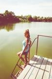 Портрет девушки стоя на мосте около воды Стоковое Фото
