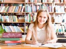 Портрет девушки студента изучая на библиотеке Стоковые Фото