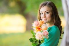 Портрет девушки с букетом роз на лесе нерезкости предпосылки Стоковое Изображение