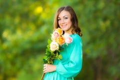 Портрет девушки с букетом роз на предпосылке запачкал листву Стоковые Фото
