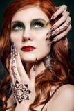 Портрет девушки с красными волосами и длинных ногтей на его стороне с красной губной помадой на половой губые и картине mehandi в Стоковые Изображения