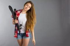 Портрет девушки с скейтбордом в студии Стоковые Изображения RF
