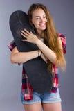 Портрет девушки с скейтбордом в студии Стоковая Фотография
