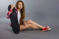 Портрет девушки с скейтбордом в студии Стоковые Фотографии RF