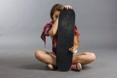 Портрет девушки с скейтбордом в студии Стоковые Изображения