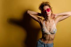 Портрет девушки с собранными волосами в верхнюю часть купальника и джинсы с розовыми стеклами стоит на желтой предпосылке она Стоковое Изображение RF