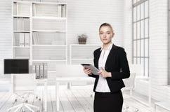 Портрет девушки с таблеткой в костюме в офисе Стоковая Фотография