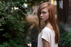 Портрет девушки redhead при веснушки и голубые глазы стоя в полу-повороте в зеленом саде смотря камеру Стоковое фото RF